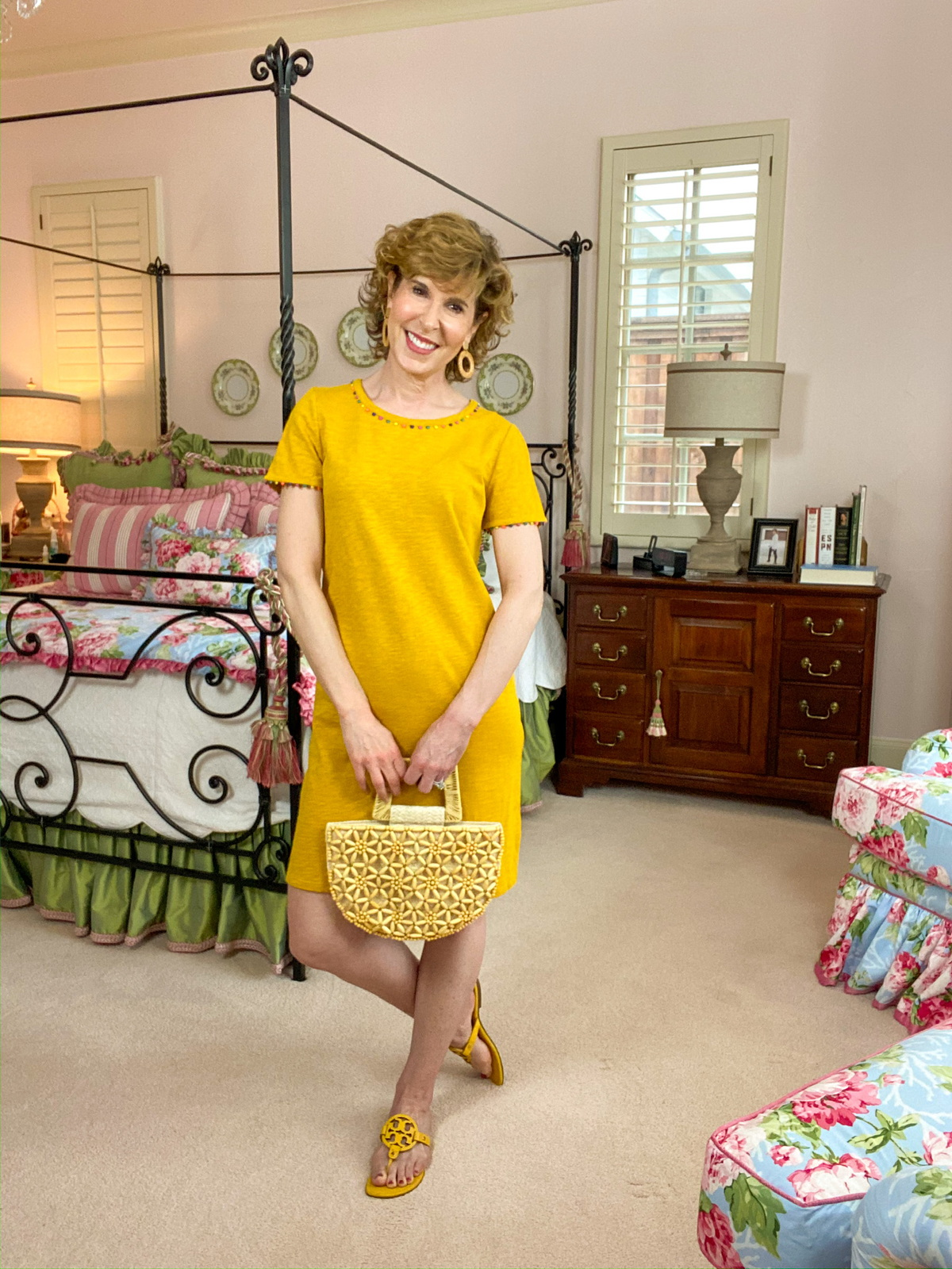 woman over 50 wearing yellow tee shirt dress standing in colorful bedroom