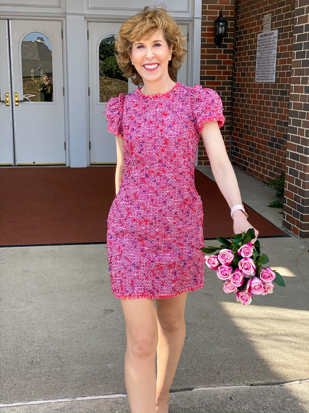 woman in pink tweed dress holding pink roses