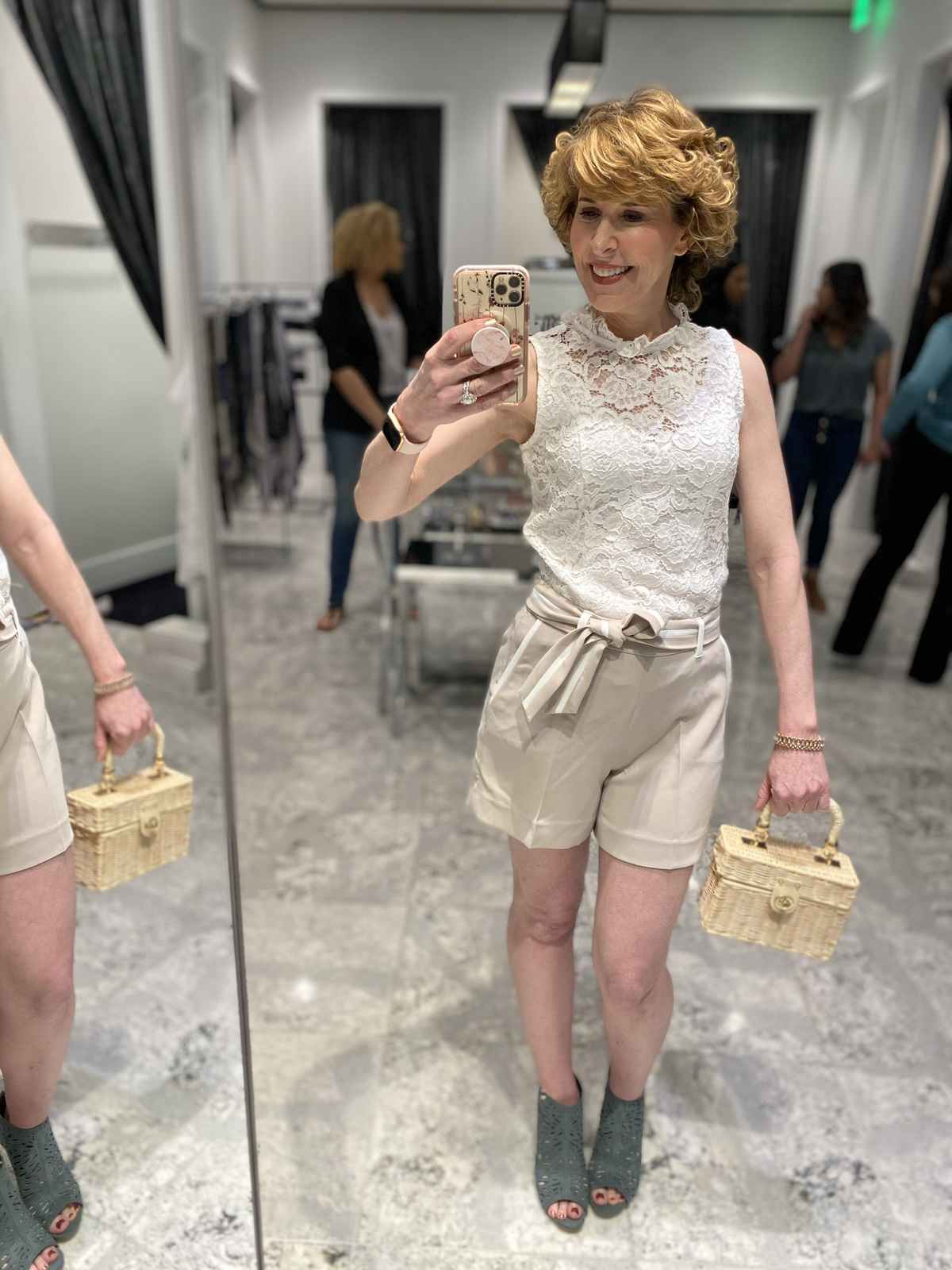 Mirror selfie of woman over 50 wearing white lace high neck top khaki shorts with white trim green shooties carrying wicker handbag doing spring wardrobe update