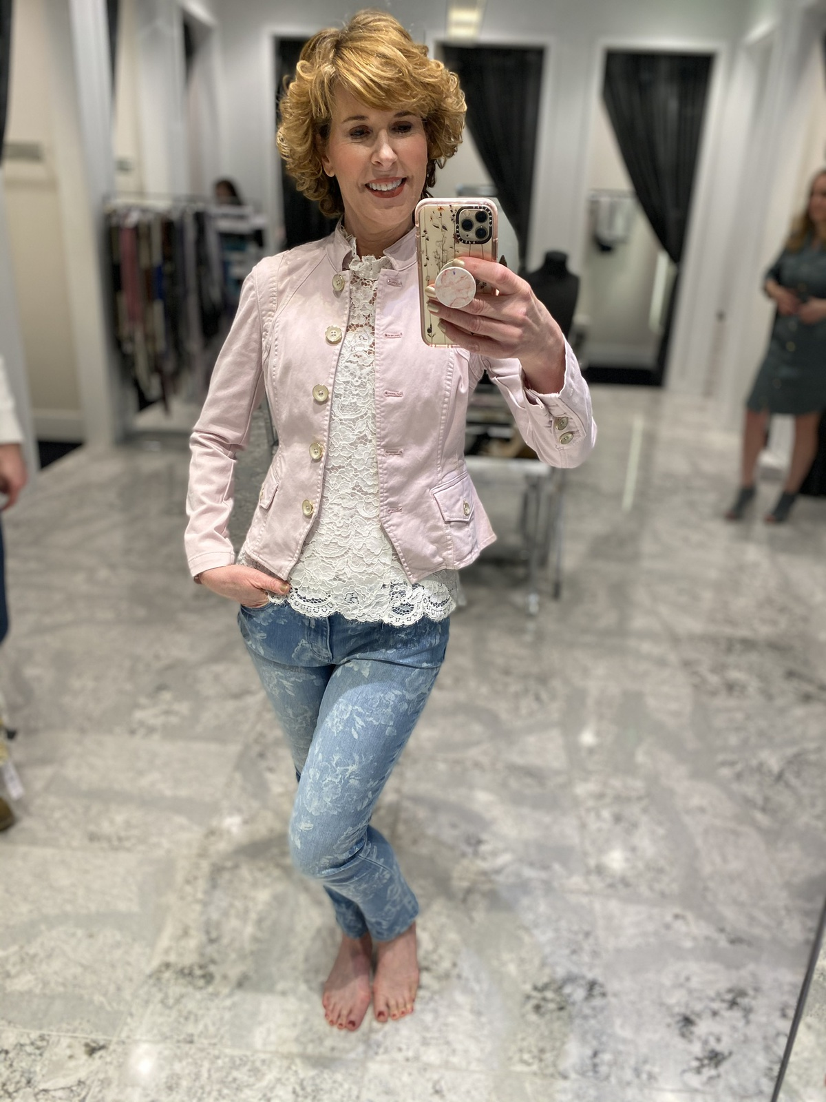 Mirror selfie of woman over 50 wearing white lace high neck top floral jeans pink pumps doing spring wardrobe update