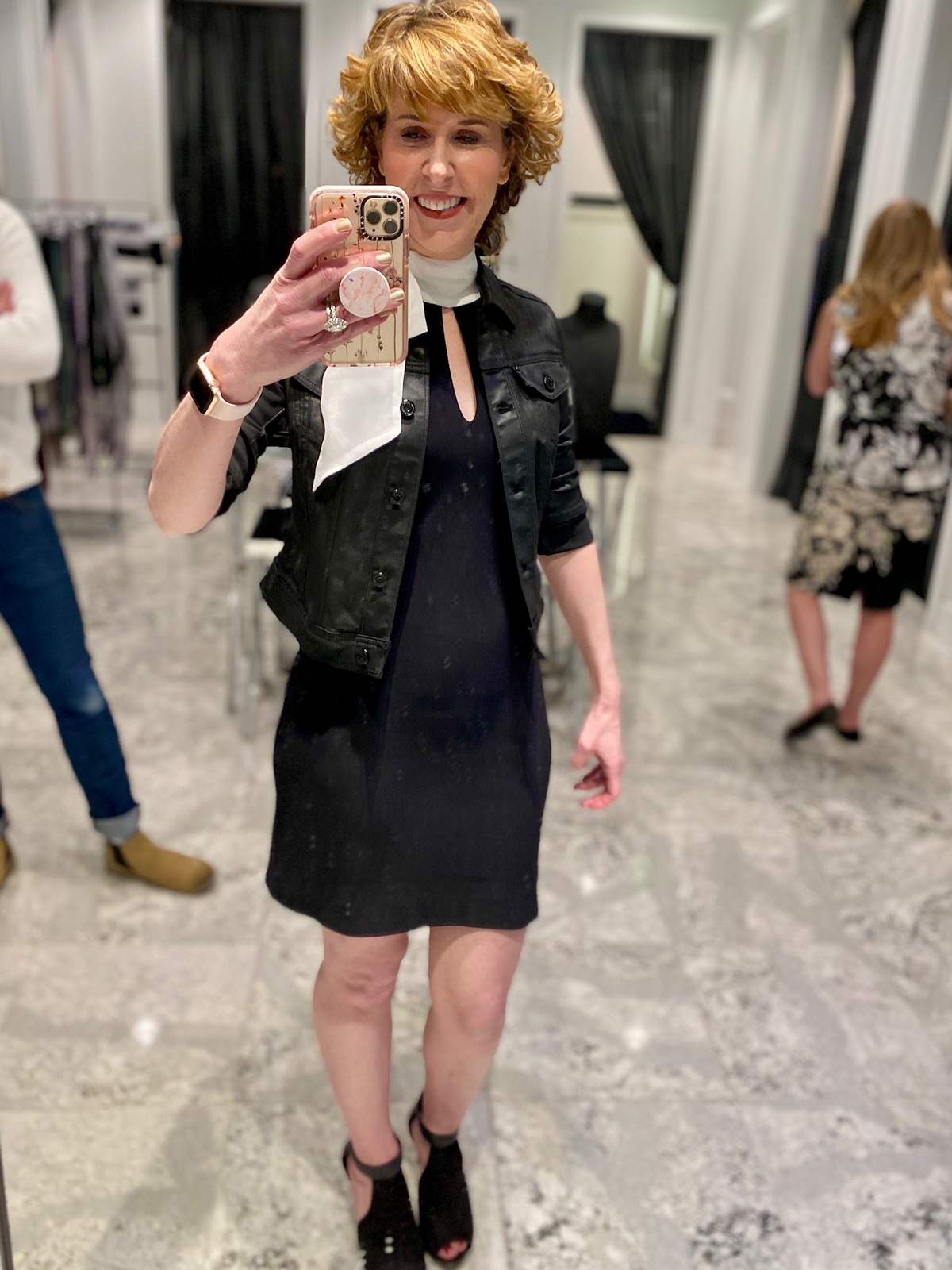 Mirror selfie of woman over 50 wearing a black dress and jacket with white bow at the neck