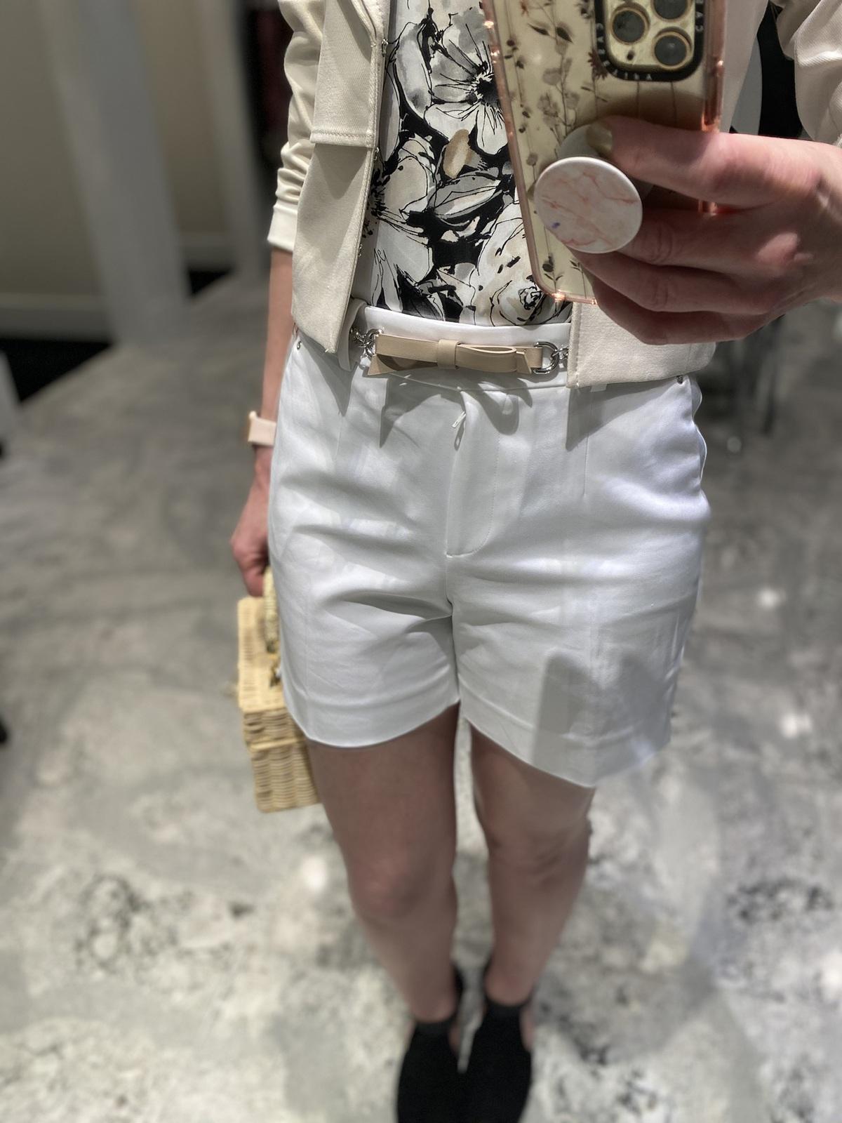 Mirror selfie of woman over 50 wearing white shorts floral shirt cream jacket carrying wicker handbag doing spring wardrobe update