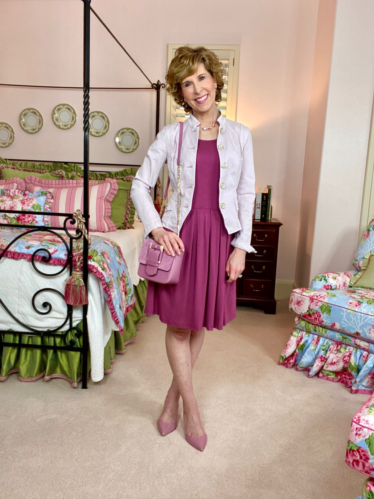 woman in pink dress and pink jacket in colorful bedroom