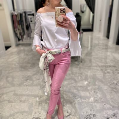 Mirror selfie of woman over 50 wearing pink jeans white off-the-shoulder top with scarf as belt pink pumps