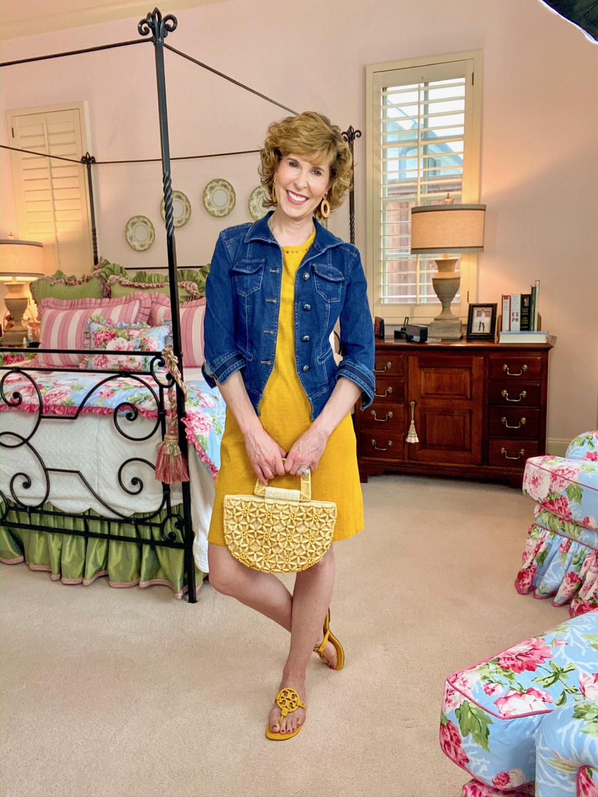 woman over 50 in yellow dress denim jacket standing in colorful bedroom