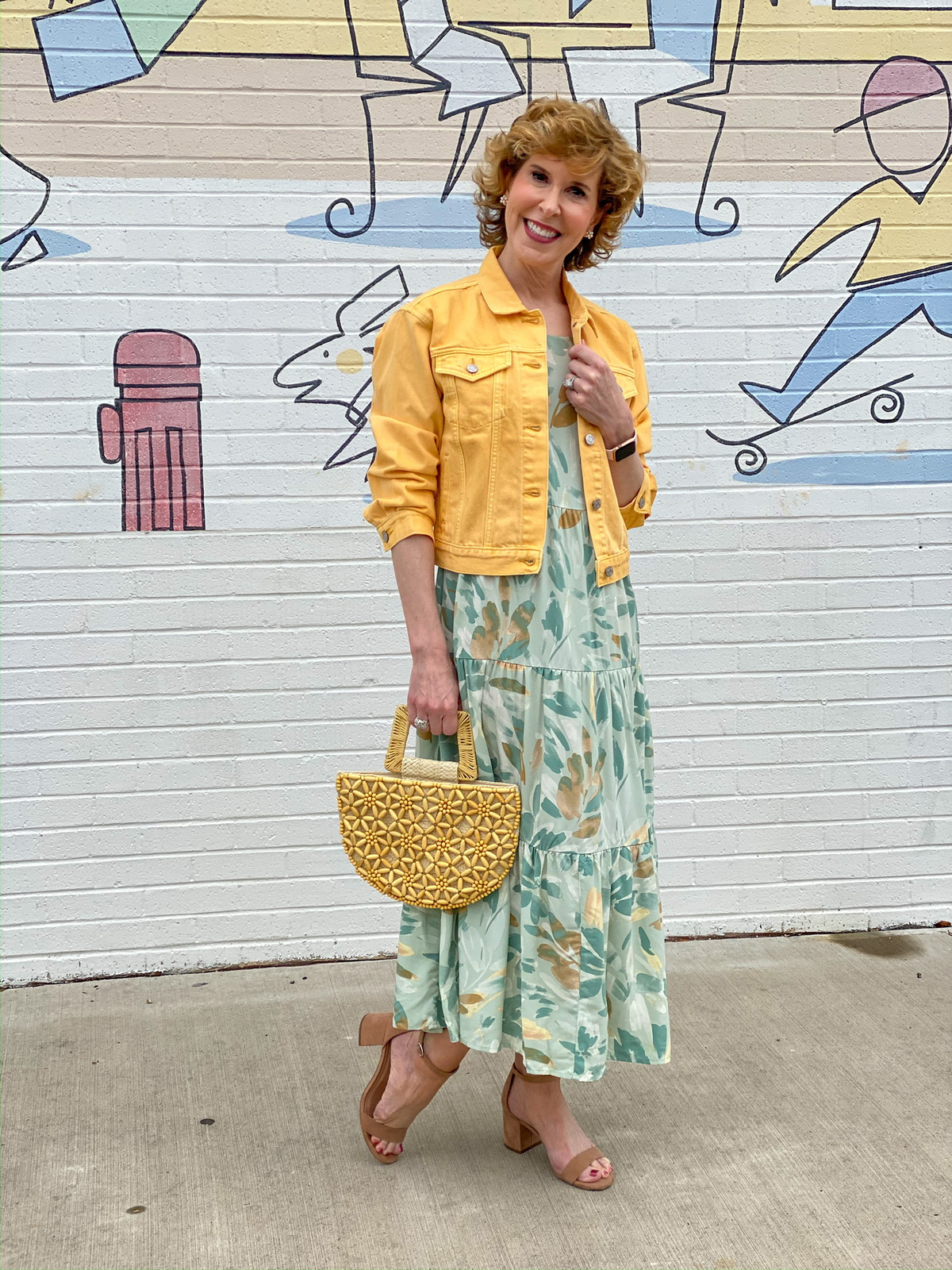 woman in green print dress and yellow jacket in front of a mural