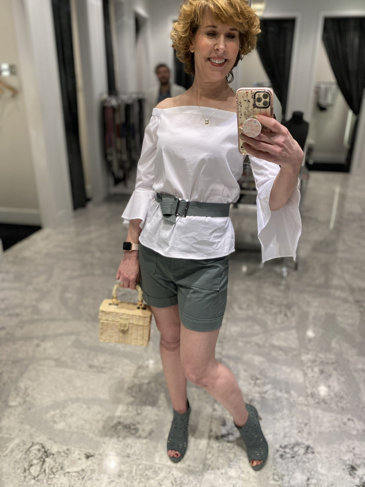 Mirror selfie of woman over 50 wearing green shorts white off-the-shoulder top with green booties carrying wicker purse