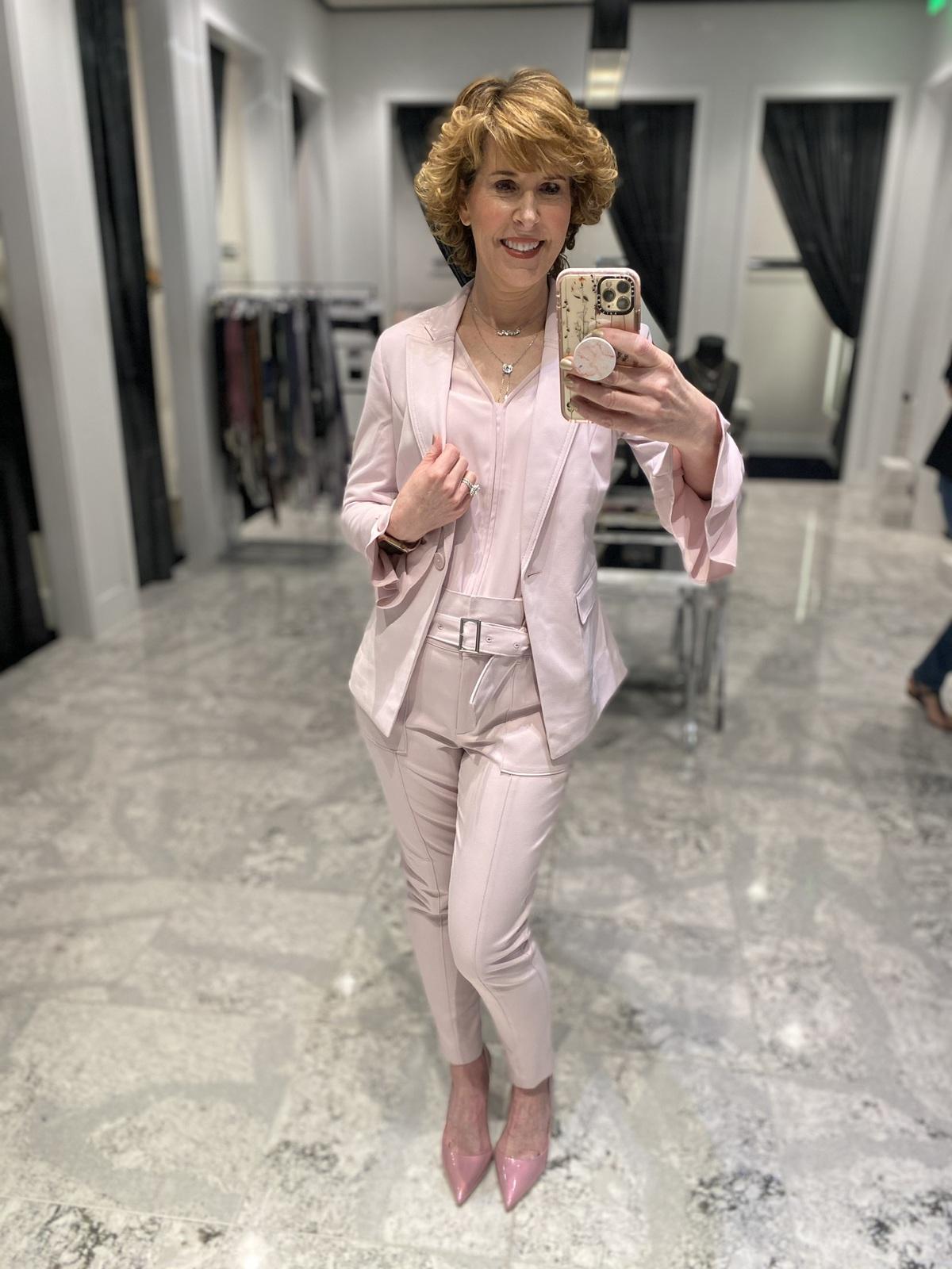 Mirror selfie of woman over 50 wearing pink ankle pants pink v-neck top, pink jacket pink pumps doing spring wardrobe update