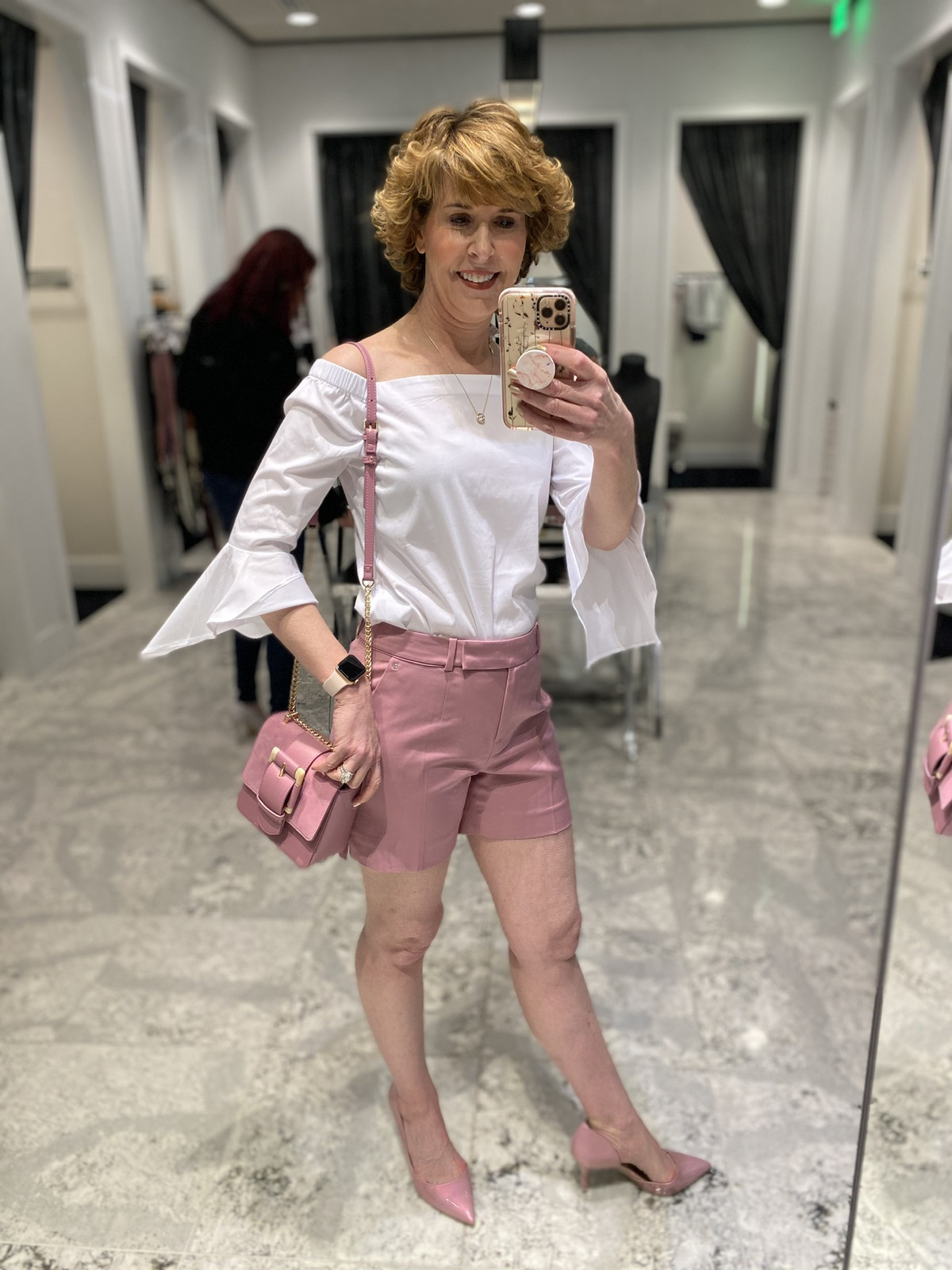 Mirror selfie of woman over 50 wearing pink shorts white off-the-shoulder top with scarf as belt pink pumps with pink purse