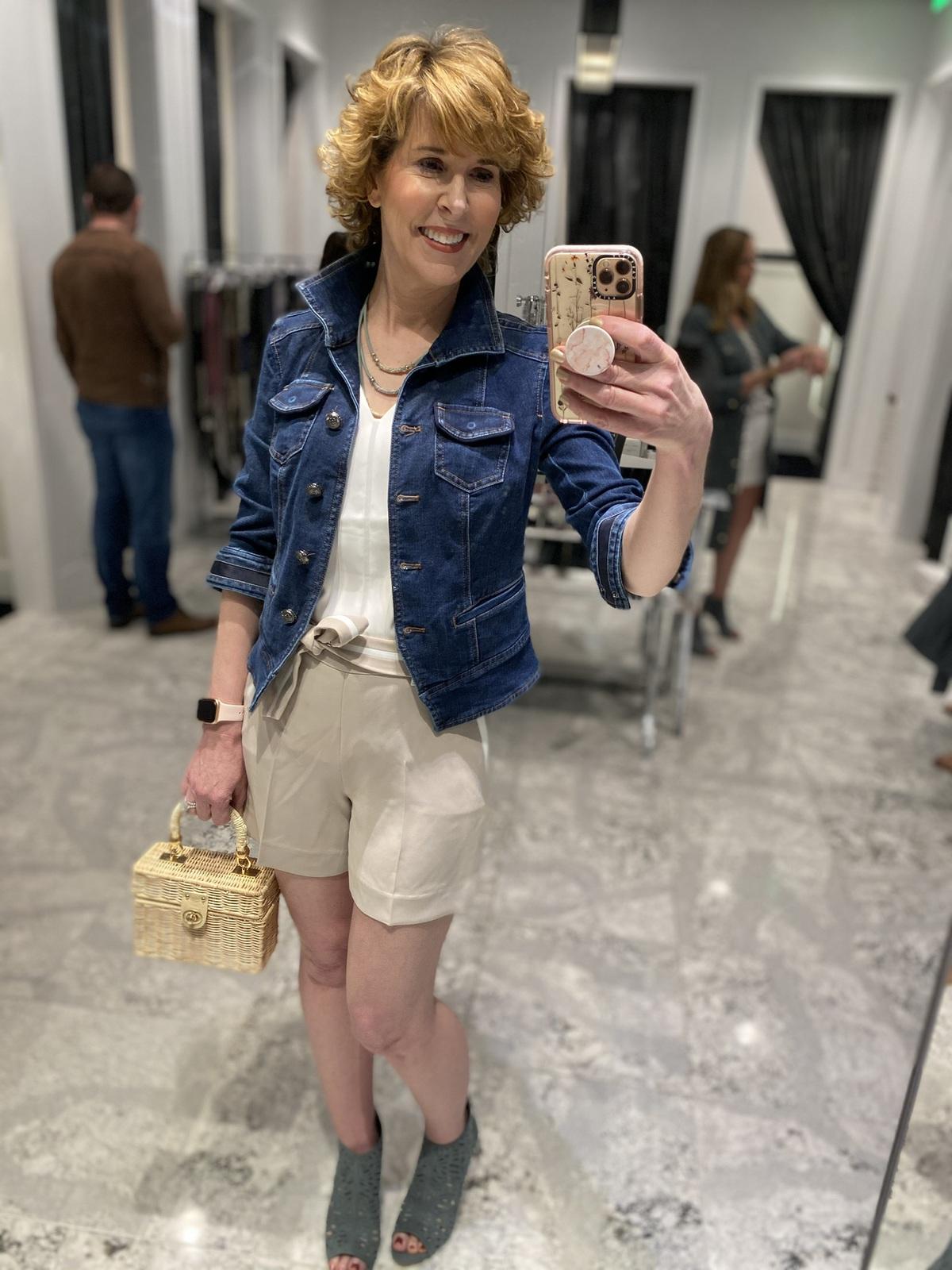 Mirror selfie of woman over 50 wearing white v-neck top khaki shorts with white trim denim jacket carrying wicker handbag doing spring wardrobe update