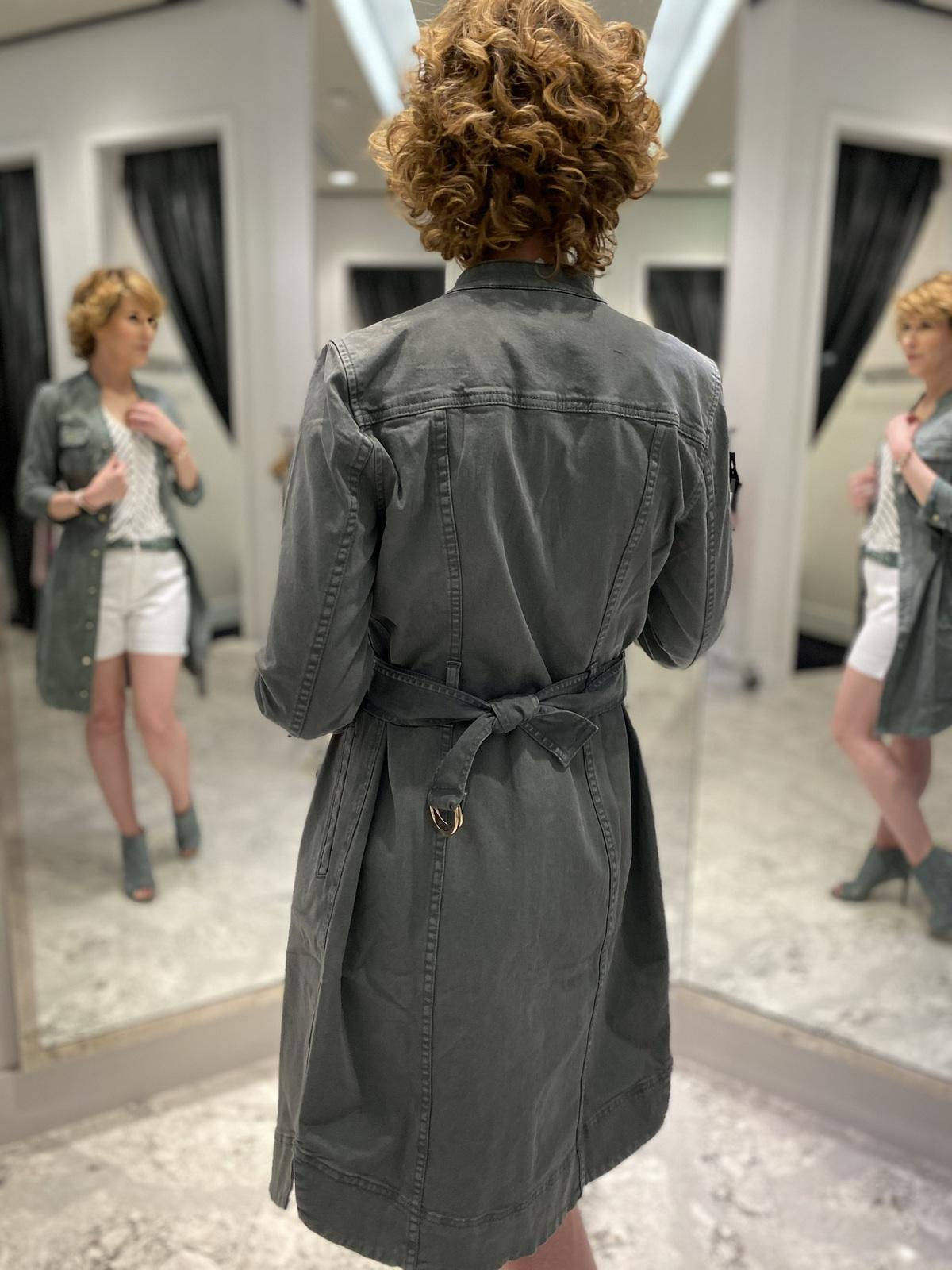 Mirror selfie of back of woman over 50 wearing green shirtdress as a jacket green laser cut booties