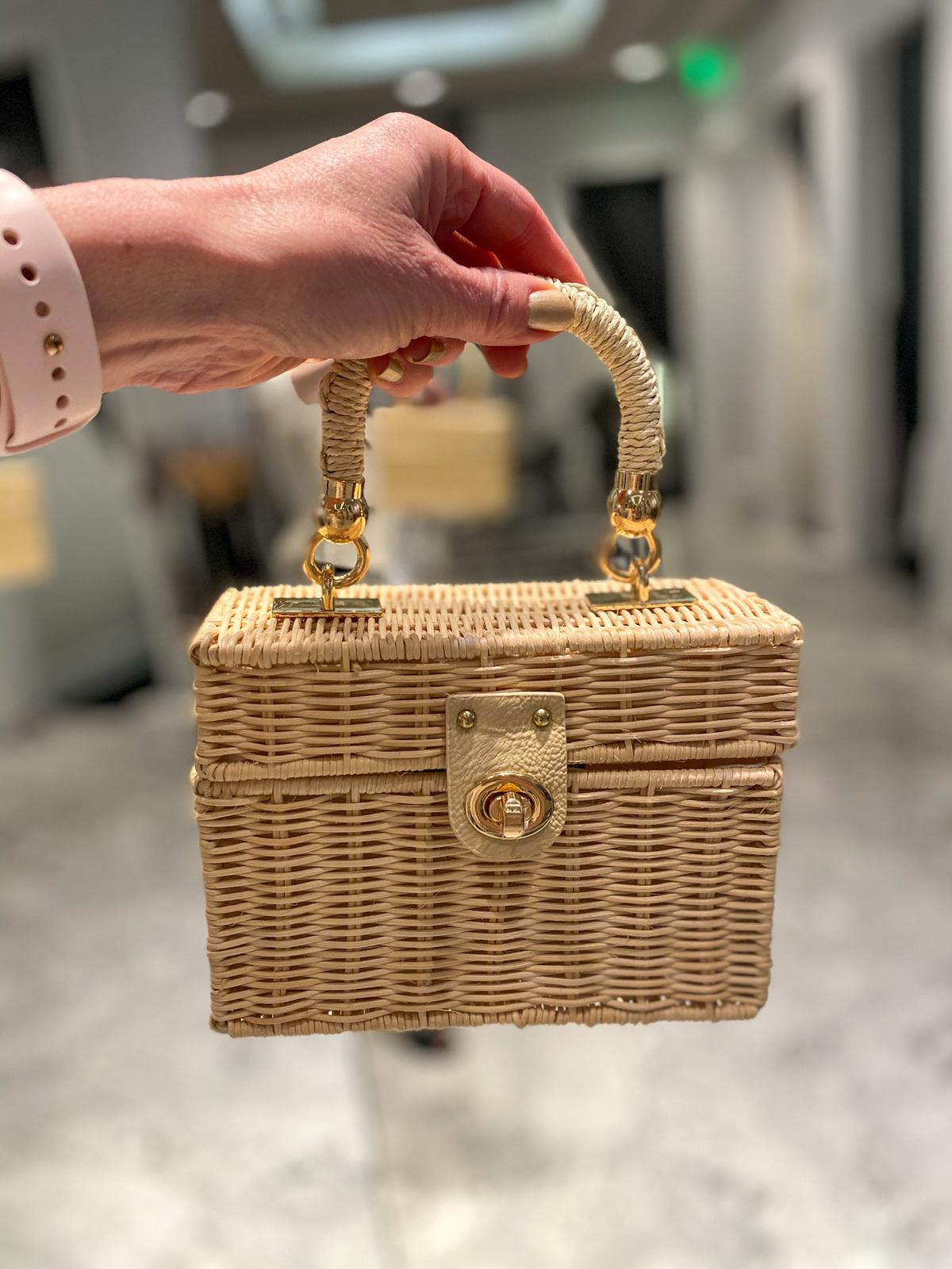 womans hand holding wicker box handbag