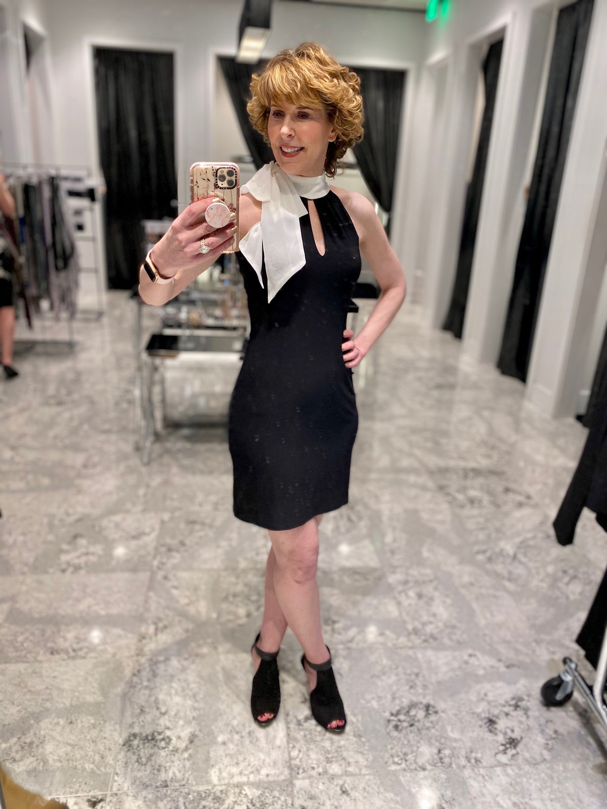 Mirror selfie of woman over 50 wearing a black dress with white bow at the neck