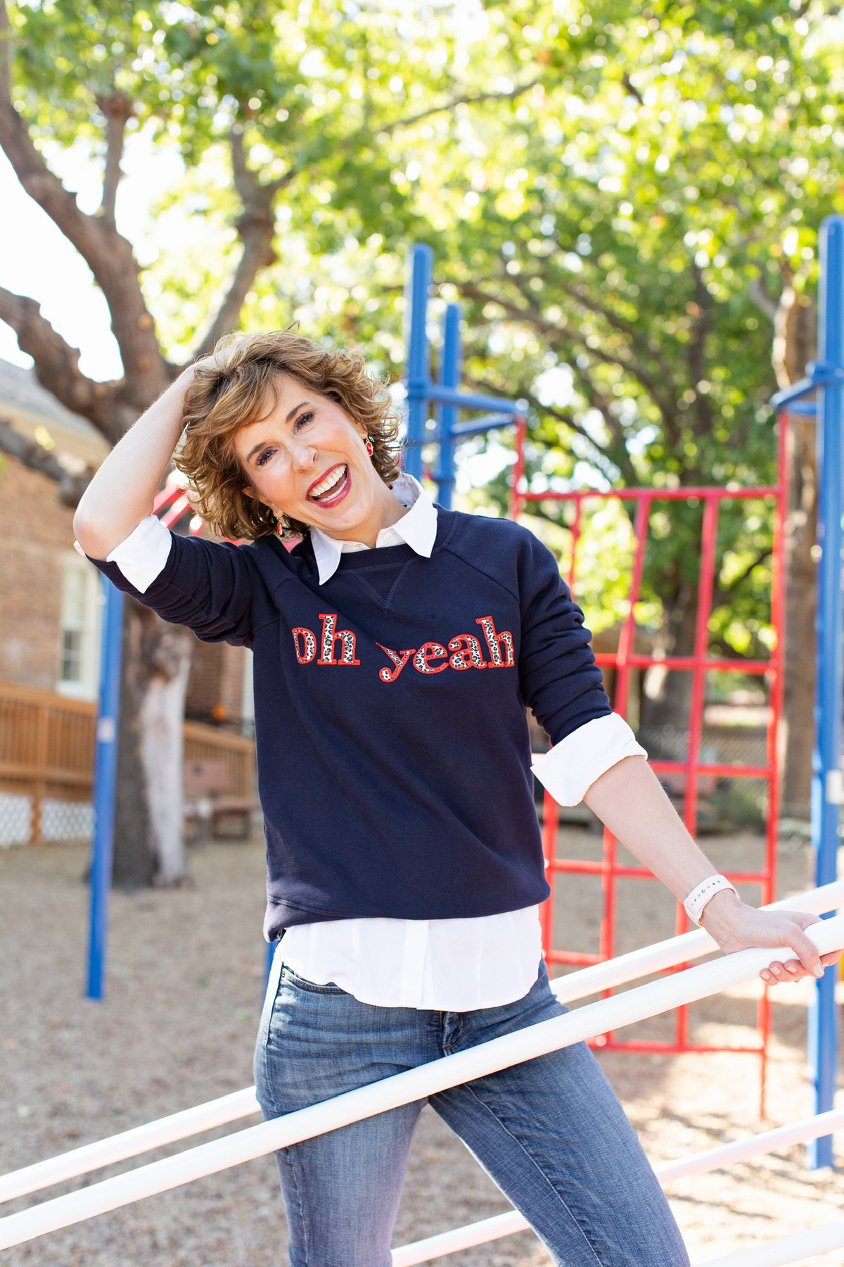 "woman over 50 wearing navy blue ""oh yeah"" sweatshirt standing on a playground"