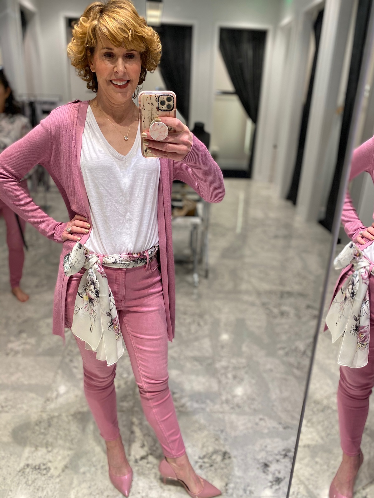 Mirror selfie of woman over 50 wearing pink jeans white v-neck tee pink long cardigan pink pumps