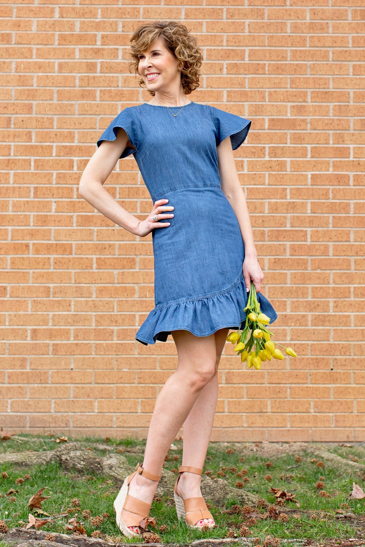 woman over 50 wearing blue chambray dress holding yellow flowers standing in front of a brick wall