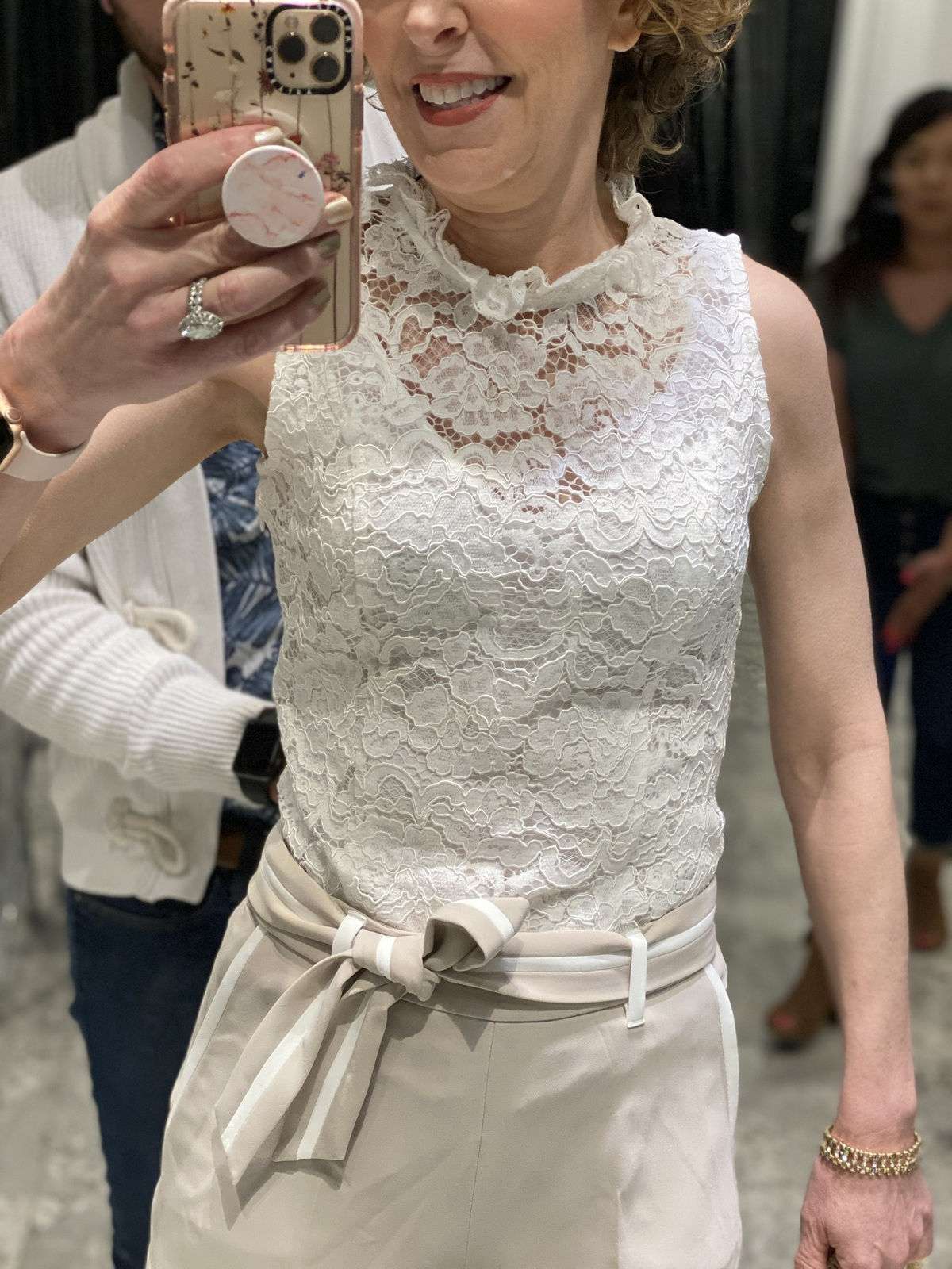 Mirror selfie of woman over 50 wearing white lace high neck top khaki shorts with white trim doing spring wardrobe update