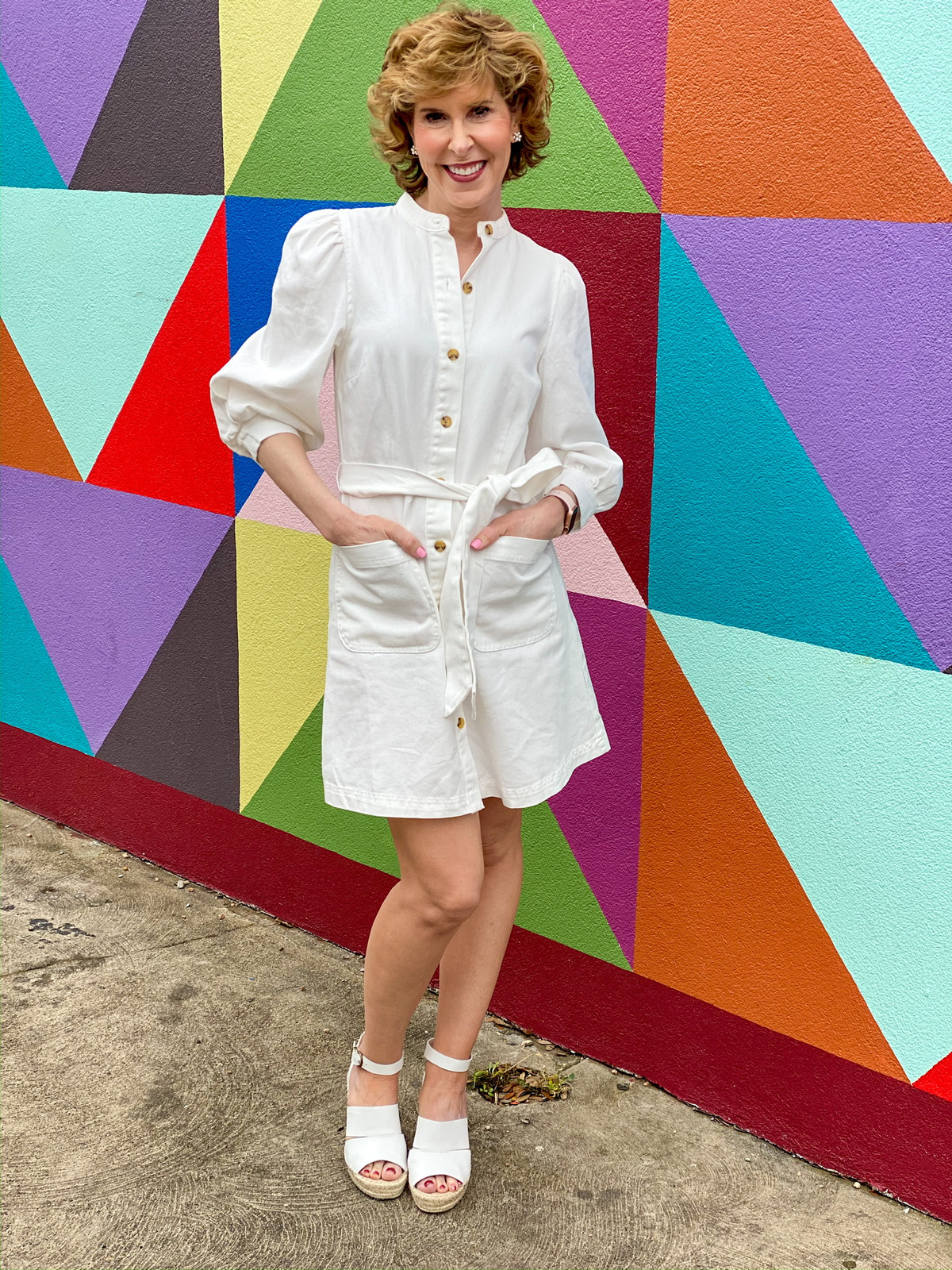 woman wearing white dress in front of colorful wall