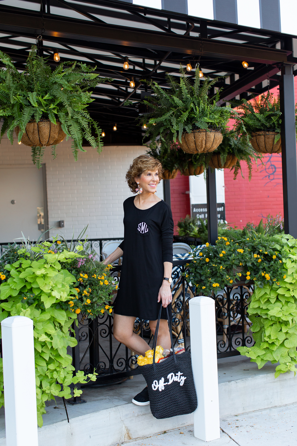 woman wearing black dress standing in front of an outdoor restaurant patio