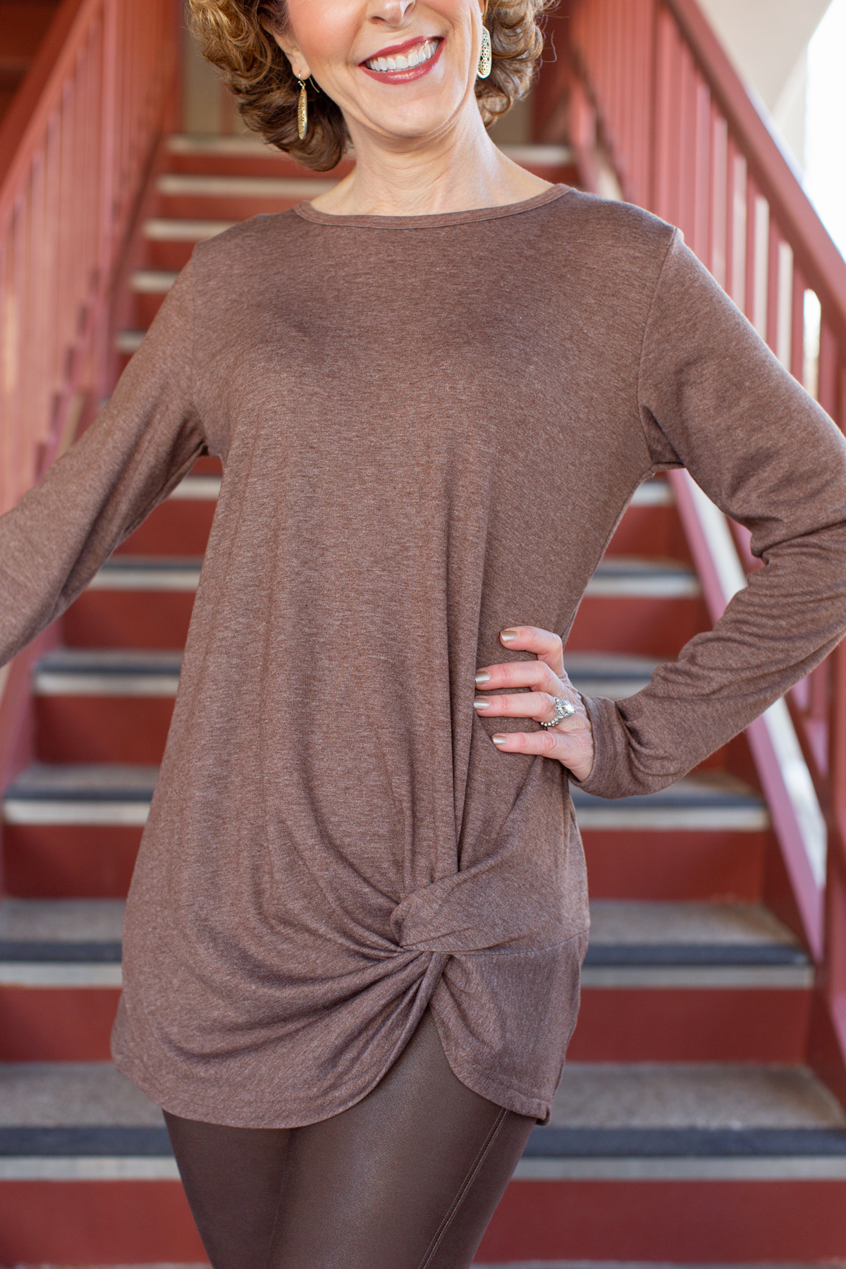 woman wearing brown tunic and leggings standing on a staircase
