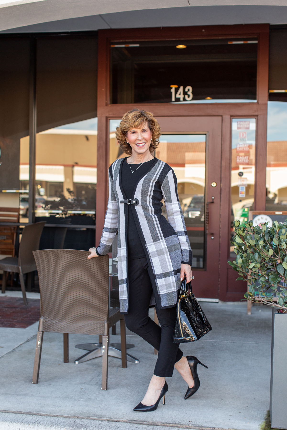 woman over fifty wearing a black plaid coat and black pants standing in front of a restaurant