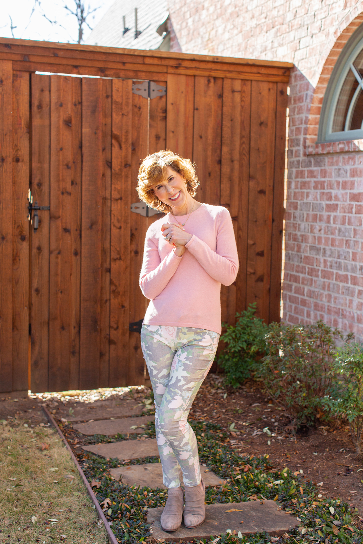 woman wearing pink sweater and floral camo jeans in front of a brown fence