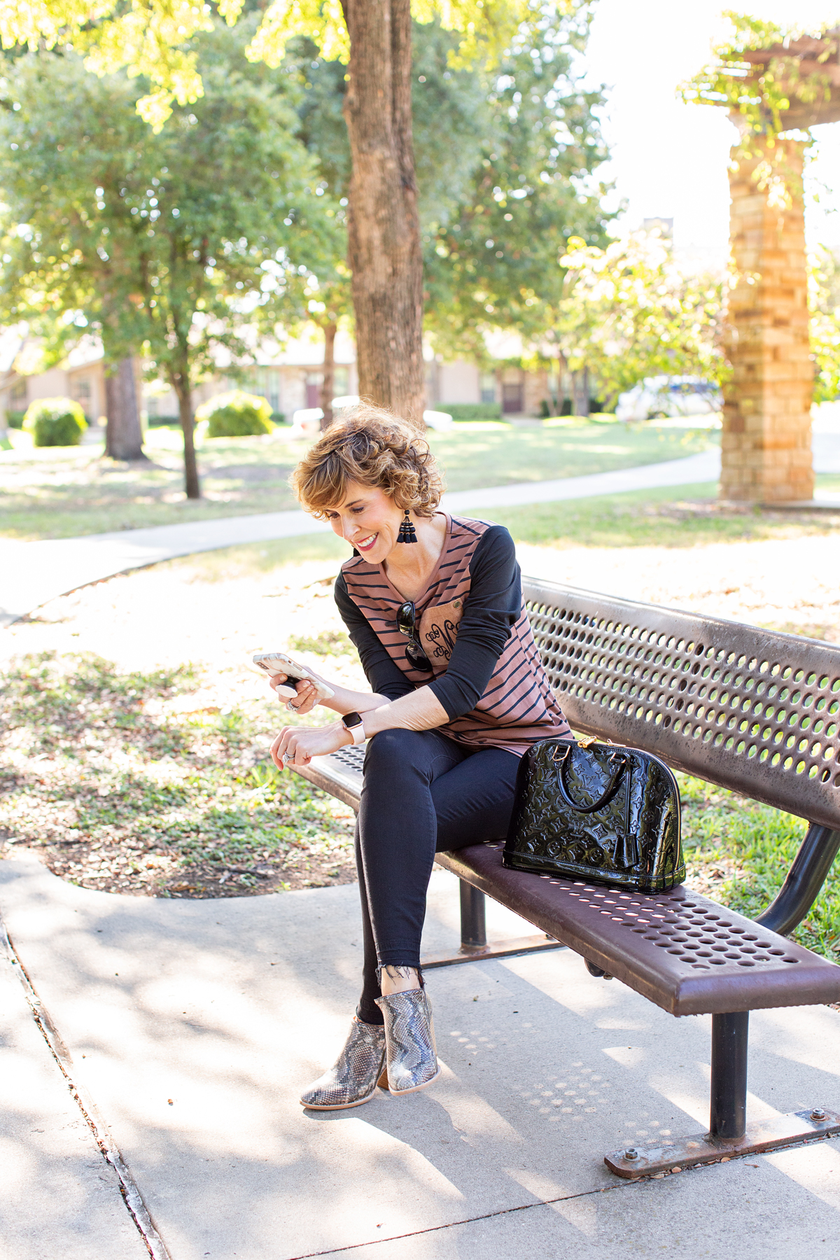 woman over 50 in brown and black outfit sitting on park bench looking at her phone