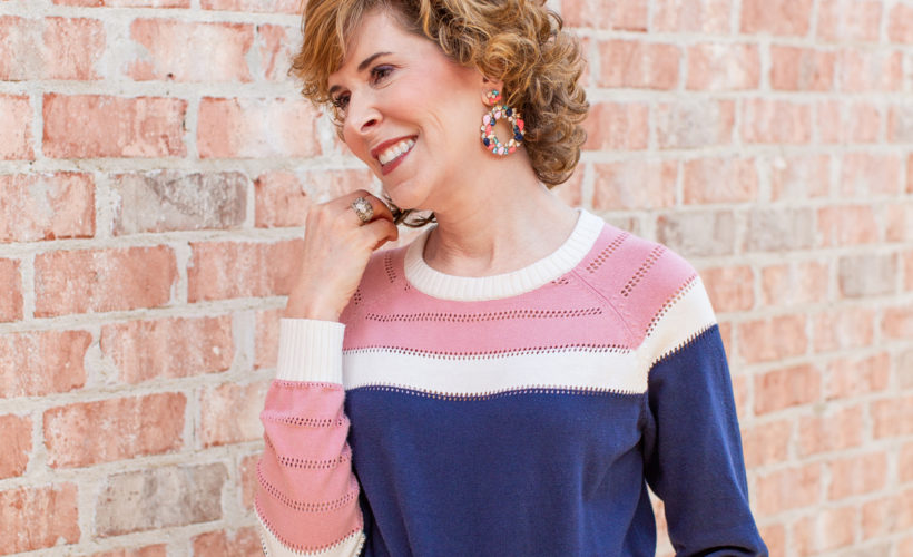 woman wearing blue and pink sweater and jeans leaning against a brick wall