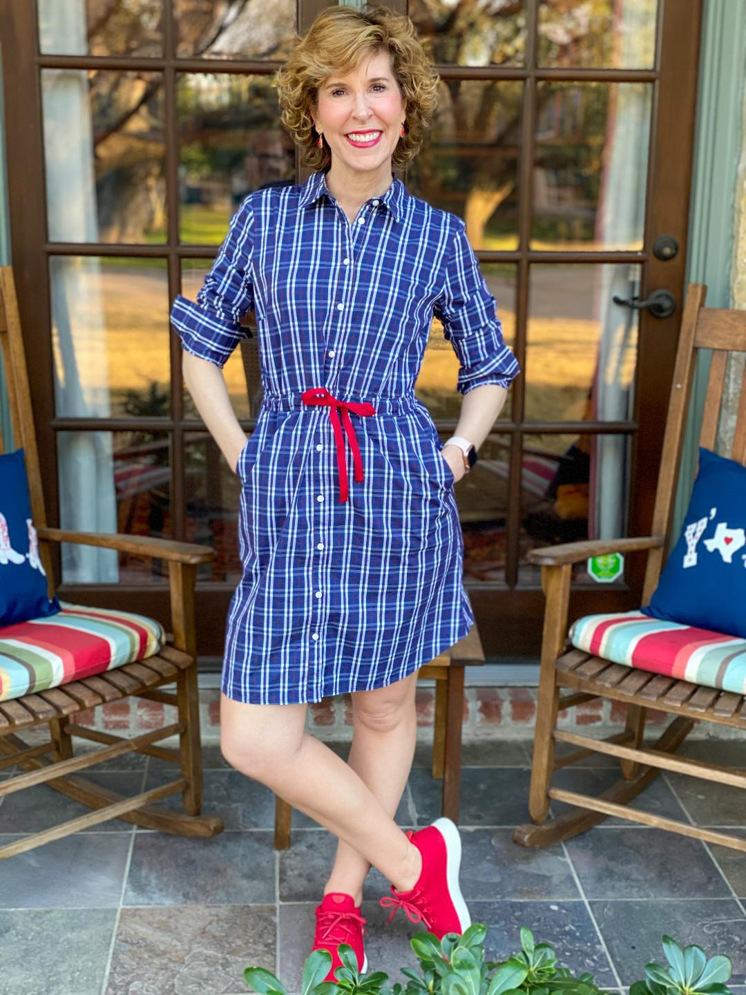 woman in blue dress with red shoes standing on her front porch