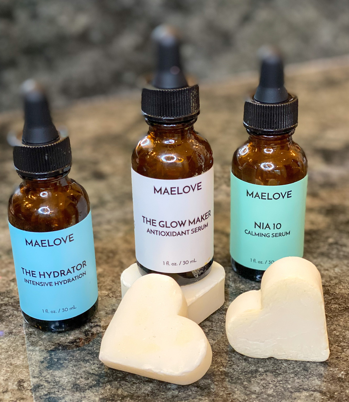 maelove skincare serums on countertop with white hearts