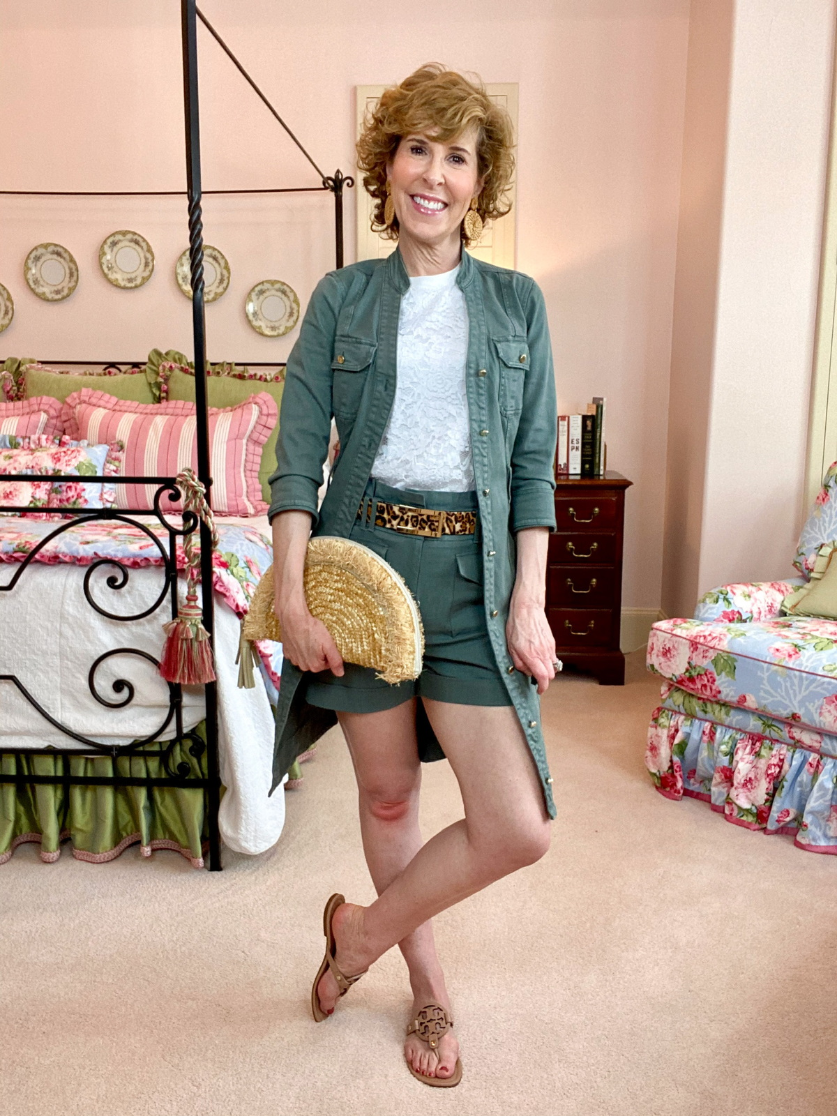 woman wearing WHBM green shirtdress open as jacket with coordinating shorts standing in bedroom