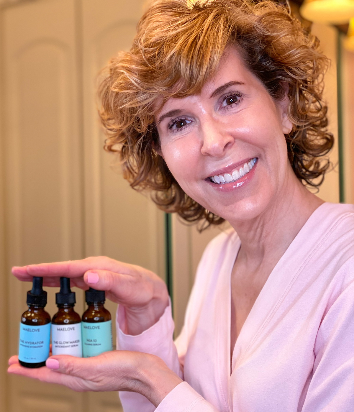 woman in pink robe holding three maelove skincare serums