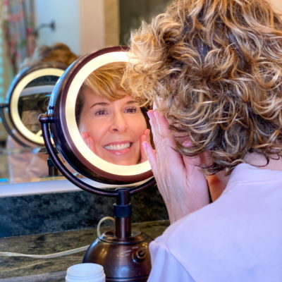 woman looking into makeup mirror applying maelove skincare