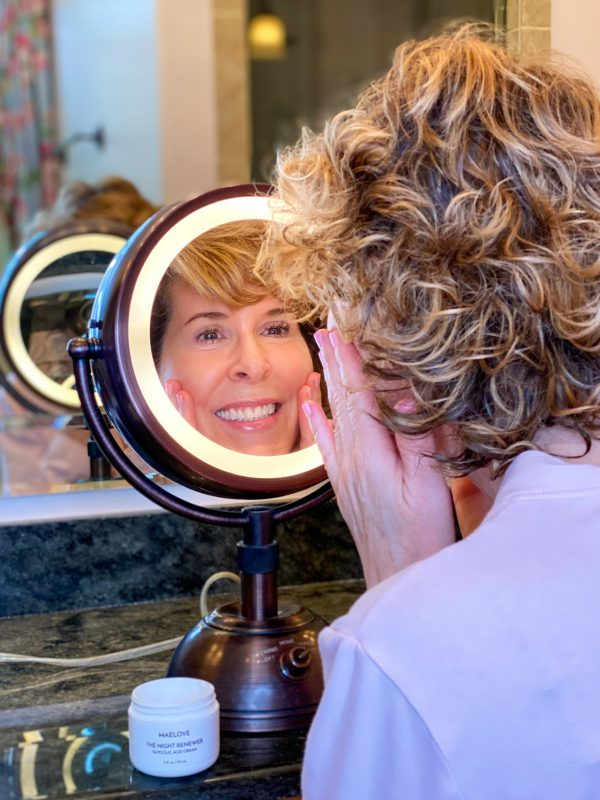 woman looking into makeup mirror applying maelove skincare