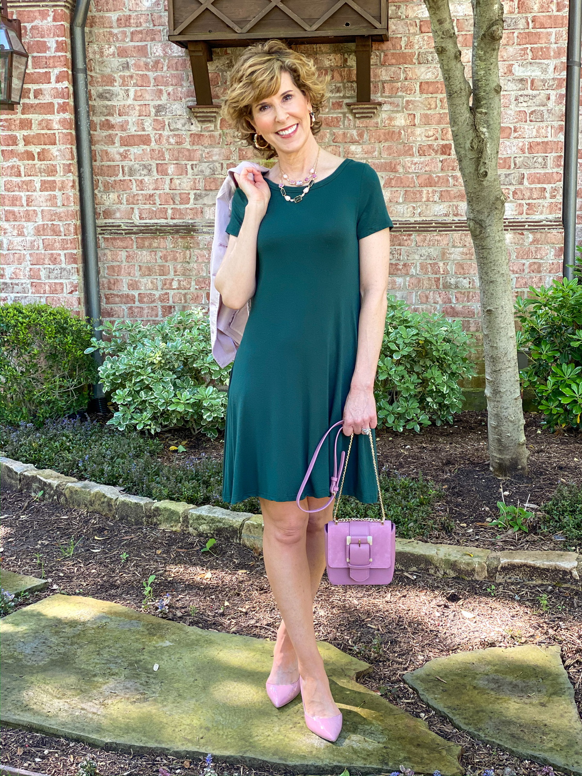 woman in green dress with pink accessories posing in her front yard
