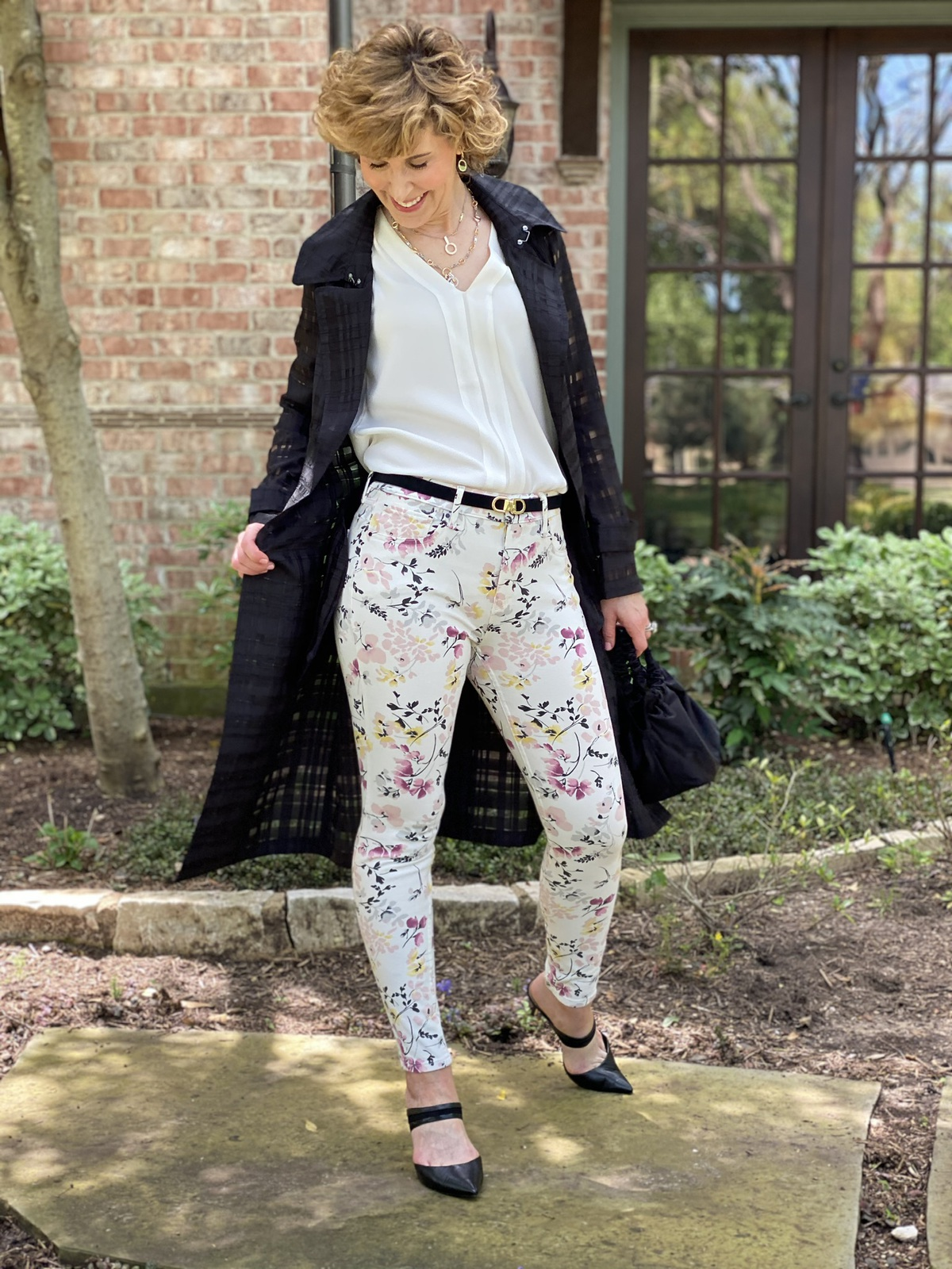 woman in black trench coat and floral pants standing in front of house