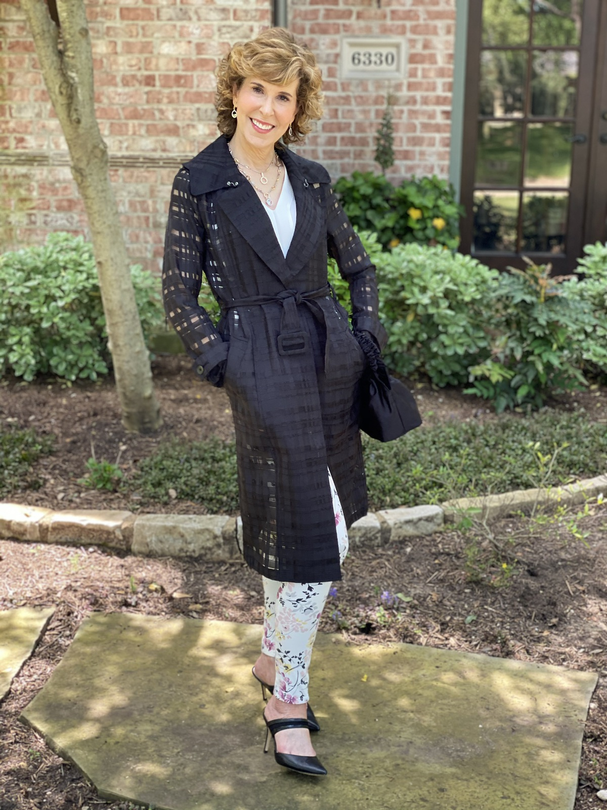 woman in black trench coat and floral pants standing in front yard