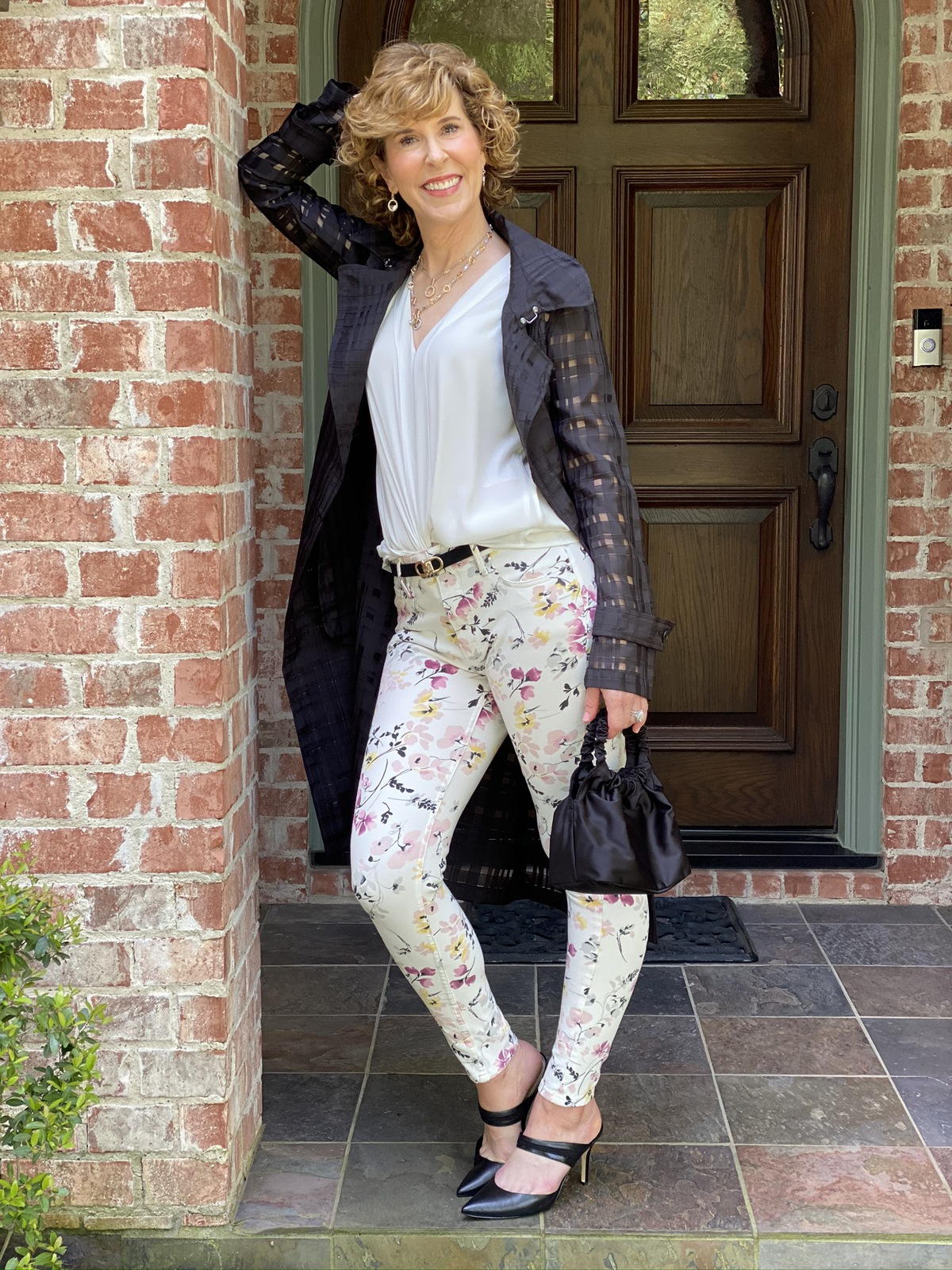 woman in black trench coat and floral pants standing in front of front door of house