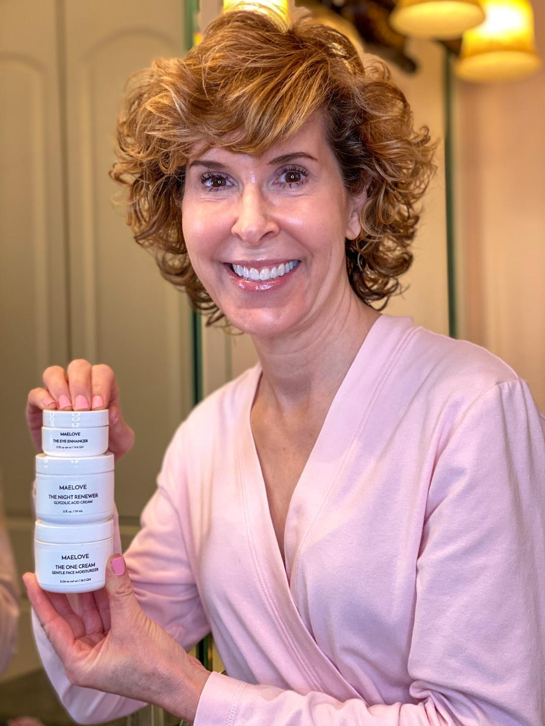 woman in pink robe holding maelove skincare lotions