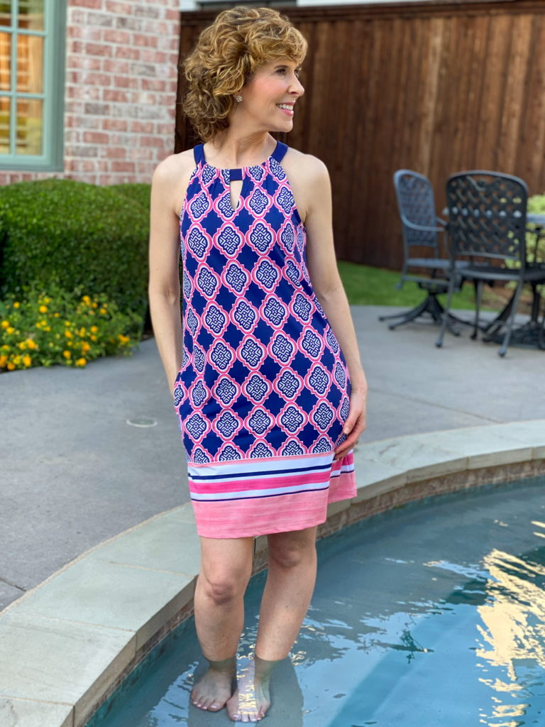 woman in blue and pink dress posing by the side of a pool