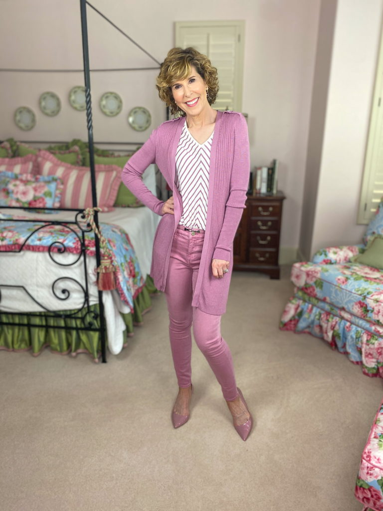 woman wearing pink jeans and long sweater standing in a bedroom