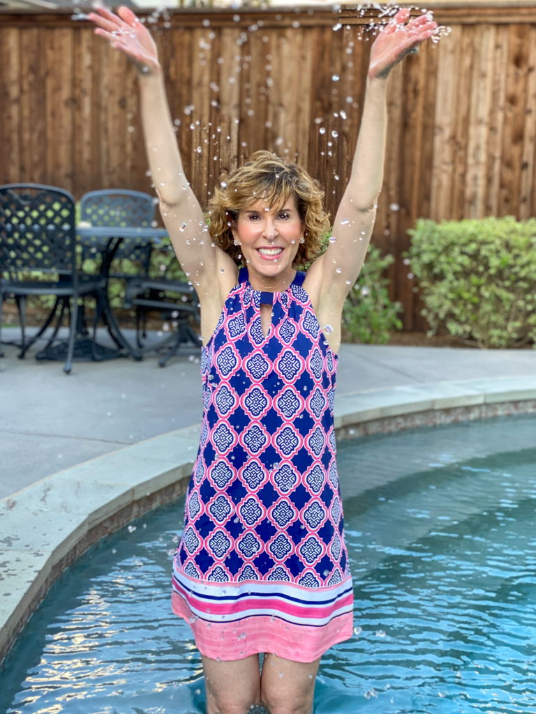 woman in blue and pink dress standing in a pool throwing water in the air