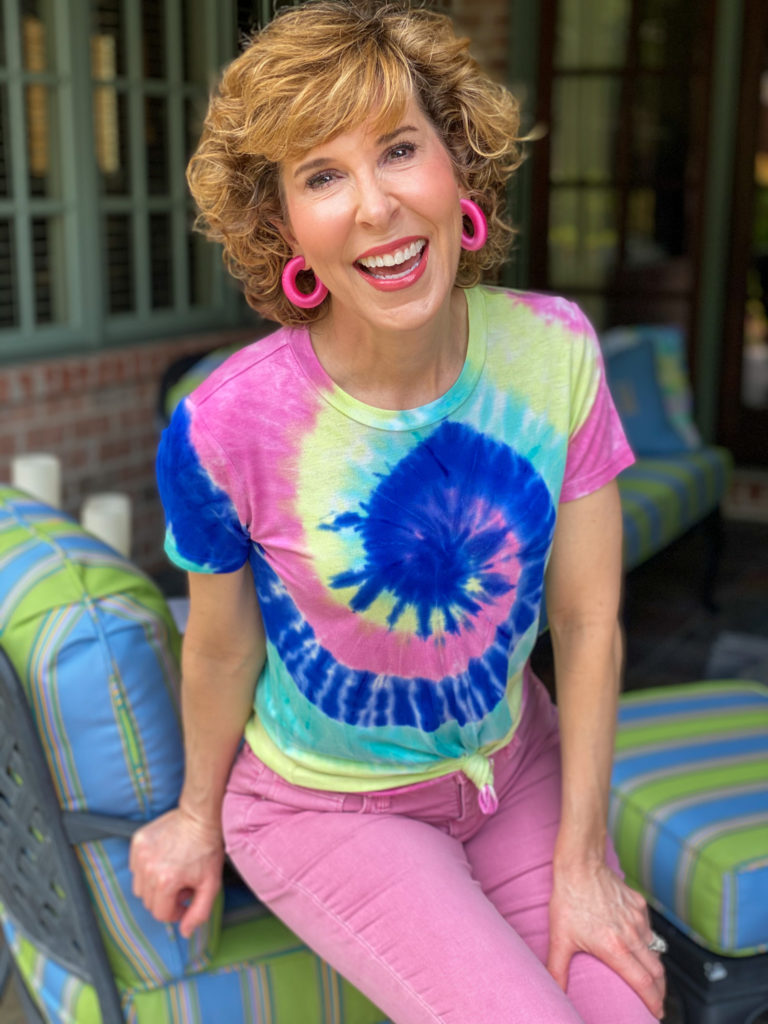 woman sitting on the edge of a chair wearing tie dye tee and bright pink earrings
