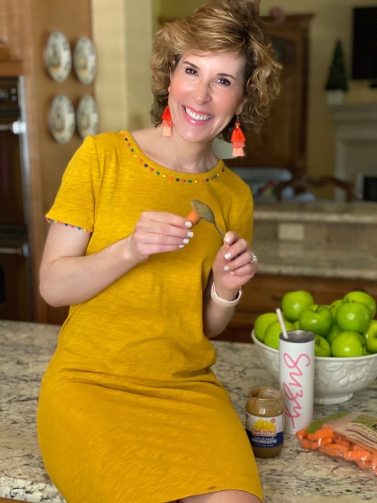 woman sitting on the kitchen counter wearing gold dress eating carrots and sun butter