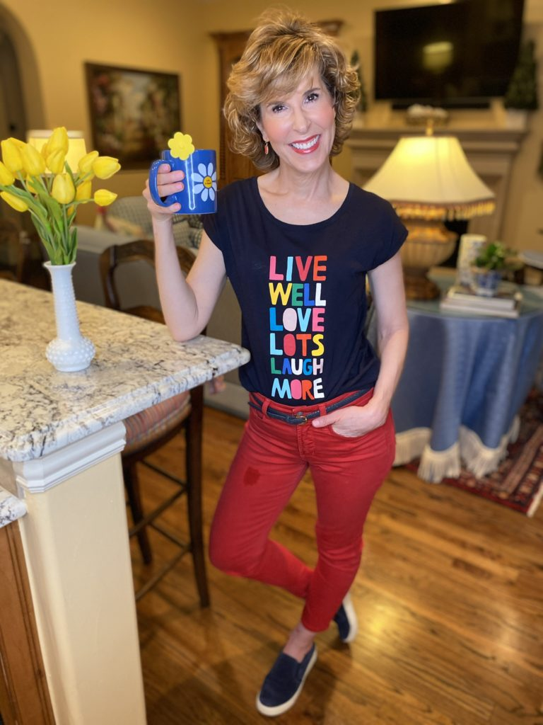 woman wearing navy graphic tee and red jeans drinking tee in her living room