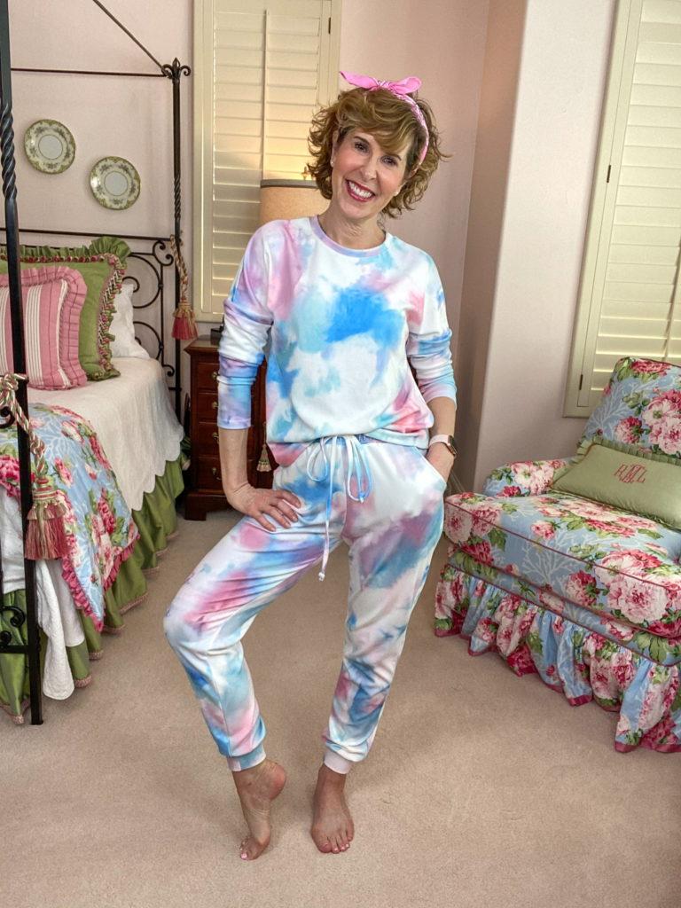 woman wearing tie dye loungewear standing in a bedroom