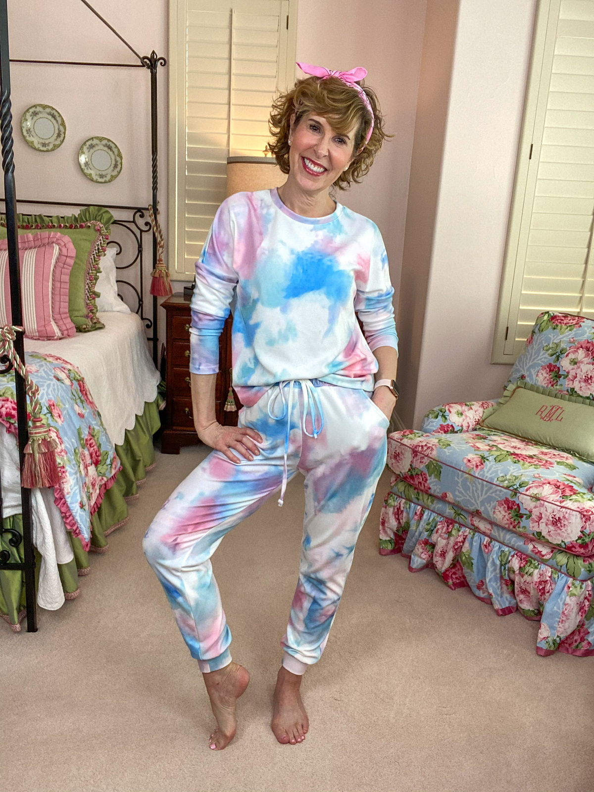 woman wearing tie dye loungewear standing in a bedroom