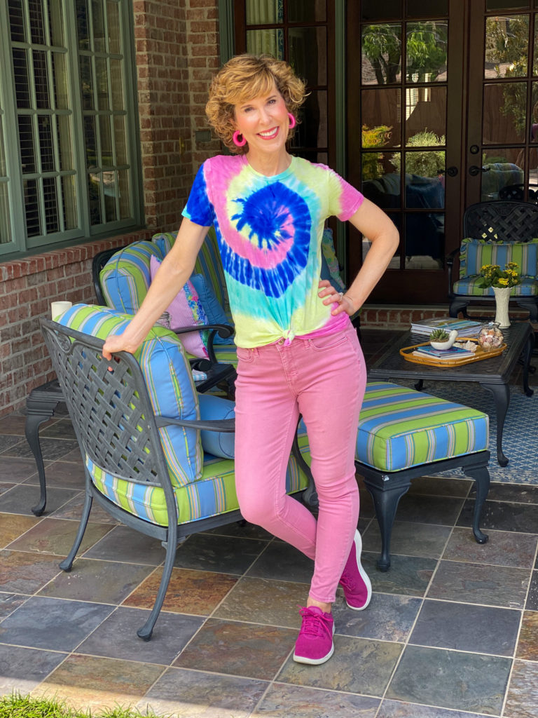 woman over 50 wearing tie die tee and pink jeans on a patio