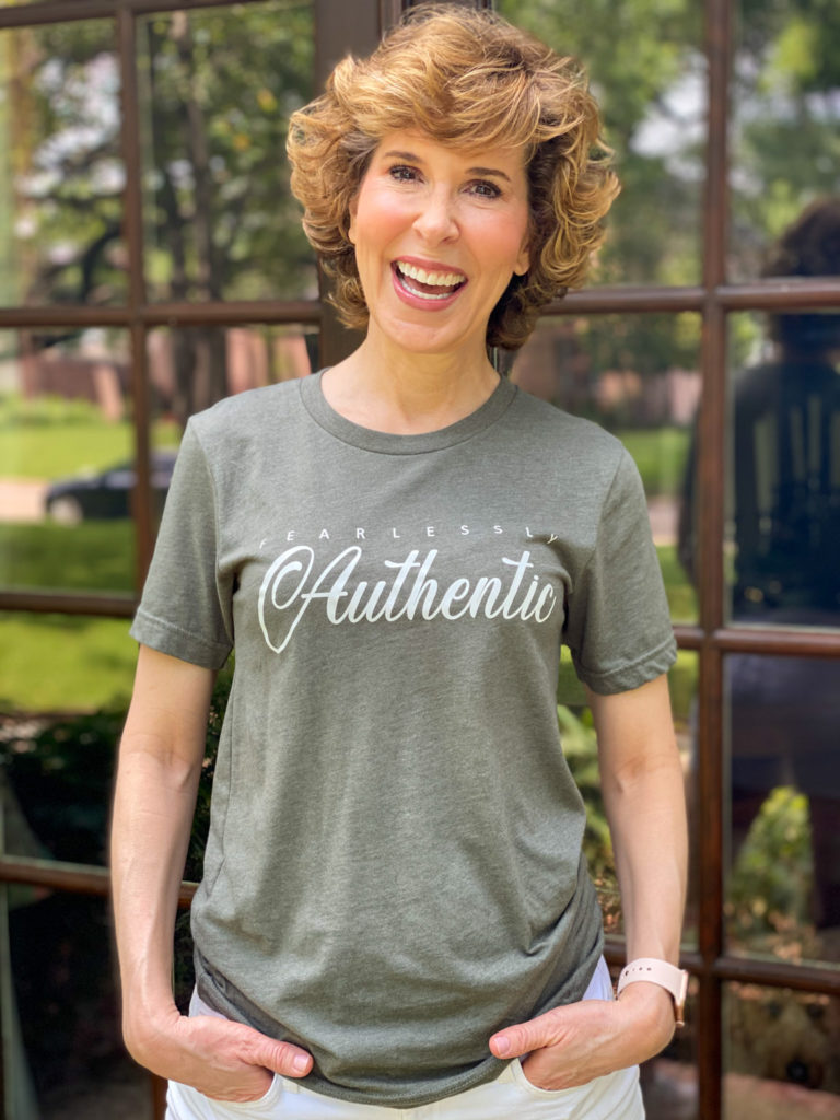 woman over 50 wearing graphic tee standing on porch in front of french doors