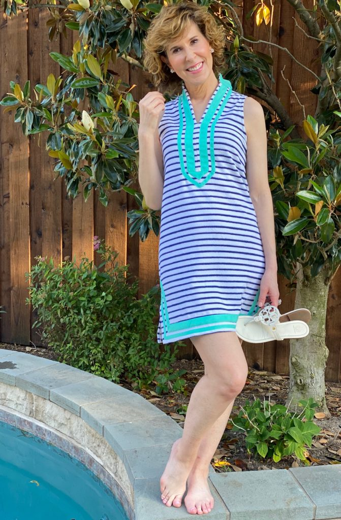 woman in blue stripe tunic dress with green trim standing by the side of a pool